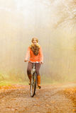 Active woman riding bike in autumn park. Stock Photography