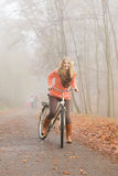 Active woman riding bike in autumn park. Royalty Free Stock Photo