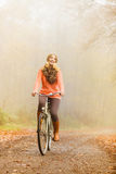 Active woman riding bike in autumn park. Royalty Free Stock Images