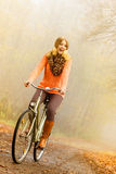 Active woman riding bike in autumn park. Royalty Free Stock Image