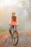 Active woman riding bike in autumn park. Active woman girl relaxing riding bike bicycle in fall autumn park. Healthy lifestyle Stock Images
