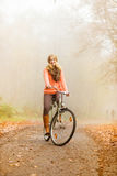 Active woman riding bike in autumn park. Active woman girl relaxing riding bike bicycle in fall autumn park. Healthy lifestyle Stock Photo