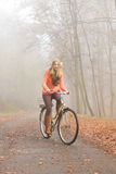 Active woman riding bike bicycle in autumn park. Stock Image