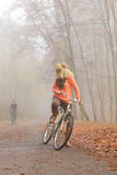 Active woman riding bike bicycle in autumn park. Active woman riding bike bicycle in foggy fall autumn park. Young girl in sweater and earmuffs relaxing Royalty Free Stock Image