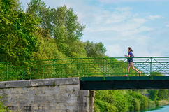 Active woman runner jogging across river bridge, outdoors running Royalty Free Stock Photography