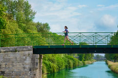 Active woman runner jogging across river bridge, outdoors running Stock Photography