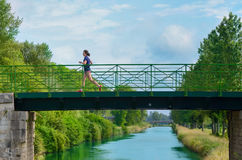 Active woman runner jogging across river bridge, outdoors running Royalty Free Stock Images
