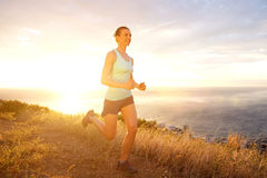Active woman running outdoors during sunset Royalty Free Stock Image