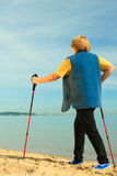 Active woman senior nordic walking on a beach. from behind Royalty Free Stock Photos