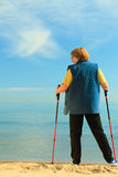 Active woman senior nordic walking on a beach. from behind Stock Images
