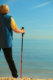 Active woman senior nordic walking on a beach. from behind Stock Image