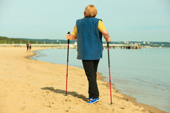 Active woman senior nordic walking on a beach. from behind Royalty Free Stock Image