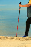 Active woman senior nordic walking on a beach. legs Royalty Free Stock Photos