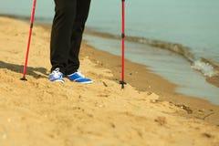Active woman senior nordic walking on a beach. legs Royalty Free Stock Photo