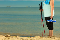 Active woman senior nordic walking on a beach. legs Stock Photography