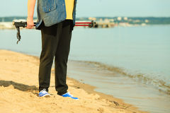 Active woman senior nordic walking on a beach. legs Royalty Free Stock Image