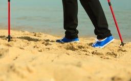Active woman senior nordic walking on a beach. legs Royalty Free Stock Photos