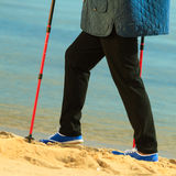 Active woman senior nordic walking on a beach. legs Stock Photos