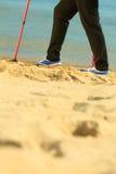 Active woman senior nordic walking on a beach. legs Stock Photo