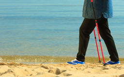 Active woman senior nordic walking on a beach. legs Stock Photo