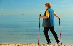 Active woman senior nordic walking on a beach Stock Photo