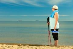 Active woman senior nordic walking on a beach Stock Image