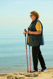 Active woman senior nordic walking on a beach Stock Image