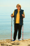 Active woman senior nordic walking on a beach Royalty Free Stock Images