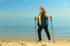 Active woman senior nordic walking on a beach Stock Photography