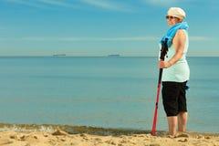 Active woman senior nordic walking on a beach Royalty Free Stock Photo