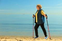 Active woman senior nordic walking on a beach Royalty Free Stock Image