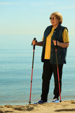 Active woman senior nordic walking on a beach Royalty Free Stock Photography