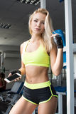 Active woman in sportswear using smart phone in the gym. Become better. Strength of will. Beautiful body. Stock Photography