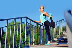 Active woman stretching her leg standing on bridge steps Stock Photography