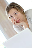 Active woman teleworking on laptop getting bored Royalty Free Stock Photography