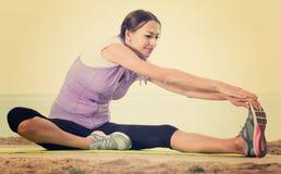 Active woman training  on sea beach on sunny morning Stock Photos