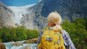 Active woman on a trip to Norway. Enjoys the beautiful Briksdal Glacier. A woman traveler looks at the famous Briksdal glacier in Norway, a back view stock photo
