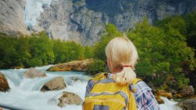 Active woman on a trip to Norway. Enjoys the beautiful Briksdal Glacier. A woman traveler looks at the famous Briksdal glacier in Norway, a back view royalty free stock photos