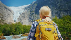 Active woman on a trip to Norway. Enjoys the beautiful Briksdal Glacier. A woman traveler looks at the famous Briksdal glacier in Norway, a back view royalty free stock image