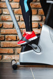 Active woman using exercise bike at the gym. Stock Images