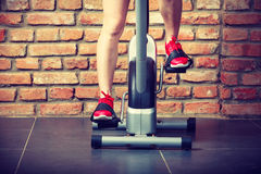 Active woman using exercise bike at the gym. Royalty Free Stock Photos
