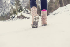 Active woman walking away from the camera through winter snow Royalty Free Stock Photo