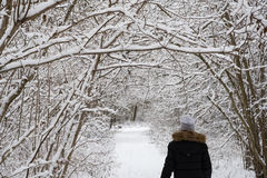 Active woman walks on a snowy footpath. Active woman is walking on a snowy footpath surrounded with snow all over stock images