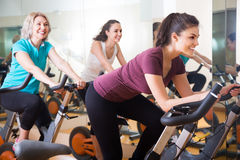 Active women of different age training on exercise bikes. Together stock images