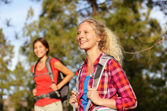 Active women - hiking girls walking in forest. Living healthy lifestyle doing outdoor activities. Female hikers trekking outside in woods wearing backpacks stock images