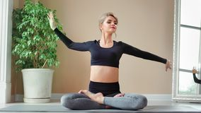 Active yoga woman sitting in lotus pose showing perfect stretching enjoying pilates workout class stock video
