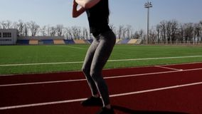 Active young attractive fit female athlete doing squats warm up stretch muscles outdoor working out outside big stadium stock footage