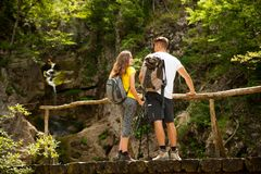 Active young cople hiking on a wooden brifge over mountain creek Royalty Free Stock Images