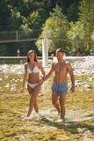 Active young couple chilling out in river on a hot summer day s. Tanding and walking in water royalty free stock photography