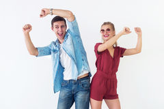 Active young couple of friends having good time, raising hands up, dancing, laughing together on white background. Stock Photos